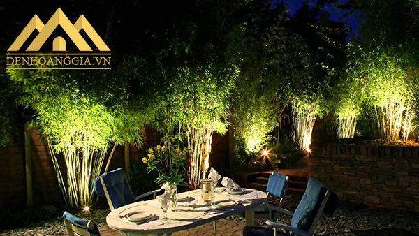 Ánh sáng chiếu từ dưới lên của đèn âm sàn ngoài trời giúp các khóm cây thêm nổi bật